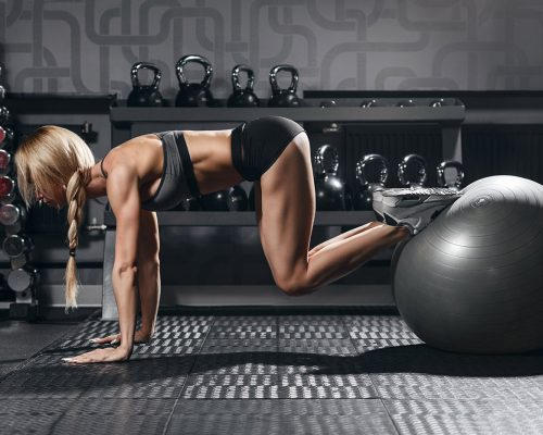 fit-blonde-female-doing-exercise-with-fit-ball-BLKDHSP-min.jpg