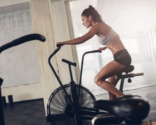 fit-young-woman-using-exercise-bike-at-the-gym-PCGRTB7-min.jpg