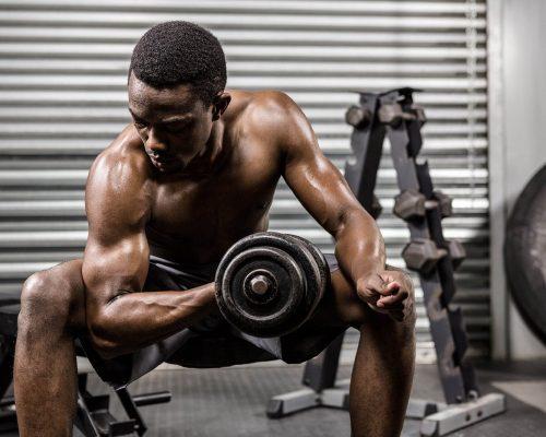 shirtless-man-lifting-dumbbell-on-bench-at-the-PQVL8YF-min.jpg